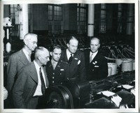 Military and Civilian Officials Viewing Manufacturing Equipment